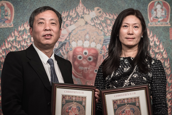 Chinese tycoon Liu Yiqian (L) and his wife Wang Wei hold framed pictures reproducing a 600-year-old Tibetan embroidered artwork called thangka at Christie's auction house in Hong Kong on March 12, 2015. The ancient Tibetan silk tapestry has broke a world auction record for Chinese art in Hong Kong after it was by bought by Liu for 348 million Hong Kong dollars (45 million USD). AFP PHOTO / Philippe Lopez (Photo credit should read PHILIPPE LOPEZ/AFP/Getty Images)