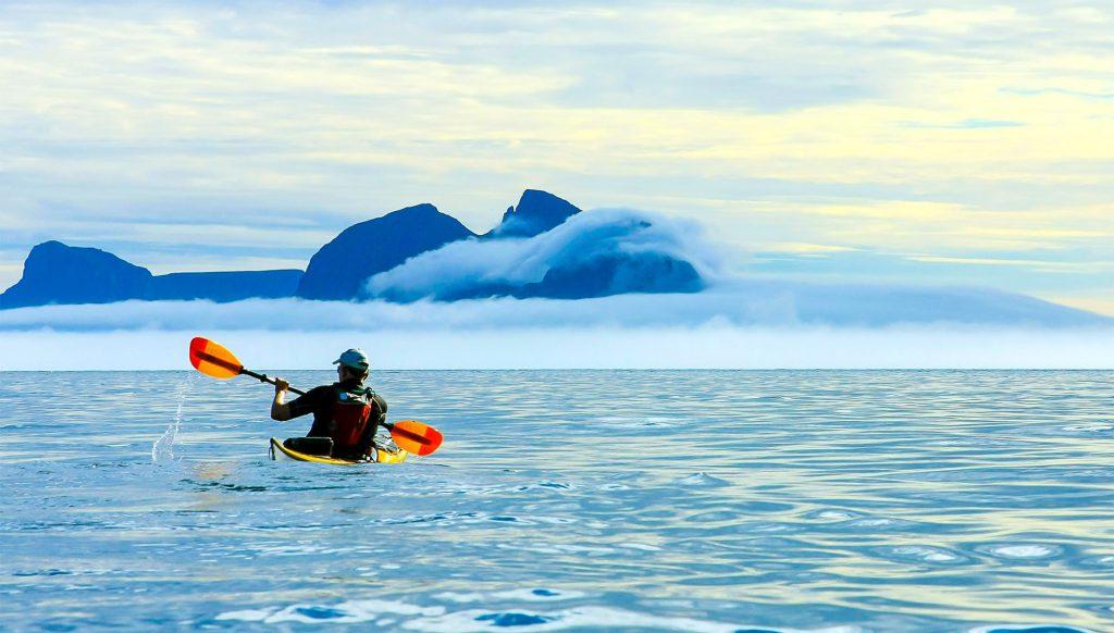 svart men kayak open sea summer
